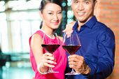 Portrait of Asian couple toasting with red wine