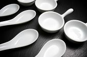 Small white spoons on a table slate
