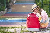 Young pretty girl sitting in the street with red suitcase. Travel concept.