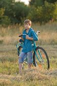 Young Boy Holding Bicycle In Farm Field