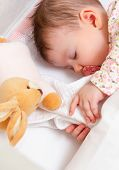 foto of sleeping  - Closeup of cute baby girl sleeping in a cot with pacifier and stuffed toy - JPG
