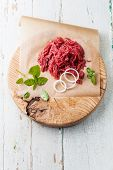 Fresh Minced Meat With Onion On Wooden Cutting Board On Blue Background