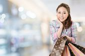 Exciting young shopping woman hold bags, closeup portrait with copyspace.