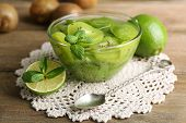 Tasty kiwi jam in glass bowl on wooden background