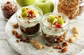Healthy layered dessert with muesli and fruits on table