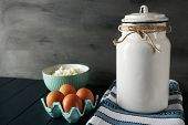 Milk can with bowl of cottage cheese and eggs on wooden table and dark background