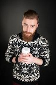 image of long beard  - Picture of young man with beard wearing sweater and holding a cup of coffee - JPG