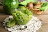 Tasty kiwi jam in glass bowl and jar on wooden table, on wicker mat background