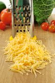 Grated cheese with grater and vegetables on wooden cutting board and white background