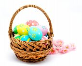 stock photo of gift basket  - Colorful handmade easter eggs in the basket isolated on a white background - JPG