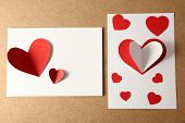 Beautiful hand made post cards  with paper hearts on color wooden background
