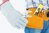 Cropped image of technician with tool belt around waist using pliers over white background