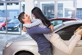 Smiling couple hugging and smiling at new car showroom