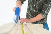 Cropped image of carpenter cutting wooden plank with electric saw against white background