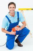 Portrait of happy carpenter holding drill machine over white background