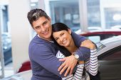 Happy couple smiling at camera and embracing at new car showroom
