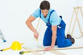 Repairman fixing screw on plank against white background