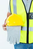 Cropped image of construction worker holding gloves and hardhat over white background