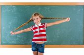 Braided student blond girl playing in green chalkboard with braids at school classroom