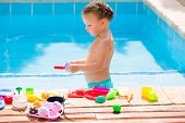 Toddler kid girl playing with food toys in swimming pool at summer vacation