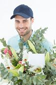 Portrait of happy delivery man with bouquet on white background