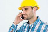Male construction worker using mobile phone against white backgorund