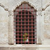 Old Arch Window With Metal Grid In A Stone Wall