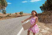 little girl hitchhiking along the street, portrait