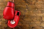 Pair of boxing gloves on wooden planks background