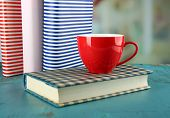 Color cup of tea with books on table, on light blurred background