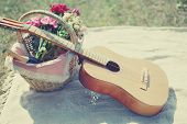 stock photo of guitar  - Guitar basket with wine and bouquet of flowers. Vintage tender background. Romance love date Valentine