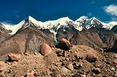 stock photo of shan  - Scenic view of rocks on the edge of Engilchek glacier with picturesque Tian Shan mountain range in Kyrgyzstan - JPG