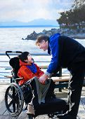 Handsome Father Talking With Disabled Biracial Son Outdoors By Lake