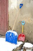 picture of snow shovel  - big and small father and child snow shovels near house wall