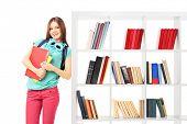 Female student leaning against a bookshelf isolated on white background