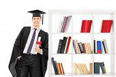 Graduate holding diploma and leaning on bookshelf isolated on white background