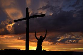 stock photo of crucifixion  - Dramatic sky scenery with a mountain cross and a worshiper - JPG
