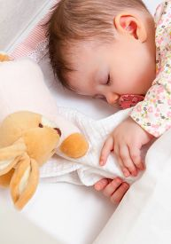 image of pacifier  - Closeup of cute baby girl sleeping in a cot with pacifier and stuffed toy - JPG