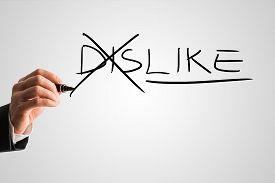 stock photo of dislike  - Man crossing through the Dis in the handwritten word Dislike on a virtual screen with a marker pen in a concept of opposites for Dislike  - JPG