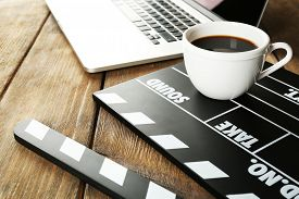 foto of clapper board  - Movie clapper with laptop and cup of coffee on wooden background - JPG