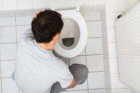image of vomiting  - High Angle View Of A Man Vomiting In Commode  - JPG