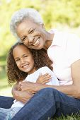 stock photo of granddaughter  - African American Grandmother And Granddaughter Relaxing In Park - JPG