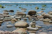 stock photo of tide  - Stack of rocks delicately balanced during low tide - JPG
