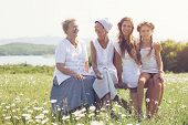 picture of four  - Four generations of beautiful women sitting together in a camomile field and smiling - JPG