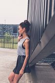 stock photo of mini-skirt  - Gorgeous young brunette in black skirt posing in an urban context - JPG