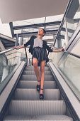 image of mini-skirt  - Gorgeous young brunette in black skirt posing on an escalator - JPG
