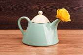 stock photo of blue rose  - Light blue teapot with flower roses on a wooden background - JPG