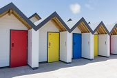 stock photo of beach-house  - Colourful doors of blue yellow and red with each one being numbered individually of white beach houses on a sunny day in Swanage - JPG