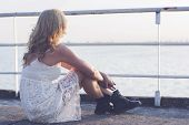 picture of woman boots  - Back of a blond woman wearing white lace dress and short black boots looking to the lake enjoying sun - JPG