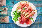 pic of melon  - salad of fresh melon with thin slices of prosciutto arugula leaves and balsamic sauce top view - JPG